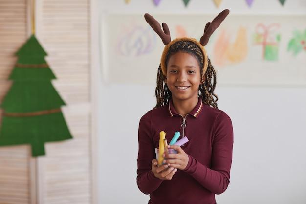Taille portrait de jeune fille afro-américaine souriante portant des bois de cerf et tenant des crayons tout en profitant de cours d'art à noël, copiez l'espace