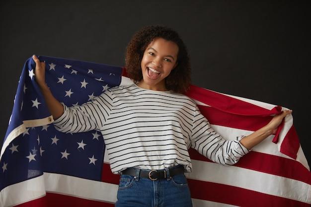 Taille portrait de jeune fille afro-américaine tenant le drapeau américain tout en posant