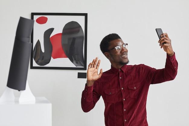 Taille portrait de jeune homme afro-américain prenant selfie photo avec peinture via smartphone à l'exposition de la galerie d'art contemporain,