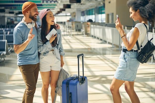 Taille portrait d'un joli couple avec bagages et carte d'embarquement posant devant l'appareil photo du téléphone portable