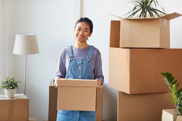 Taille portrait of smiling asian woman holding boîte en carton posant dans une nouvelle maison tout en emménageant