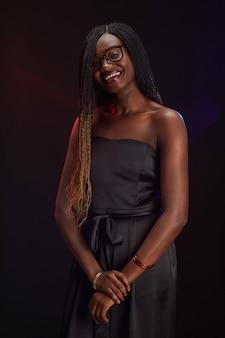 Taille verticale jusqu'à portrait de jeune fille afro-américaine souriante portant des lunettes tout en posant à la fête