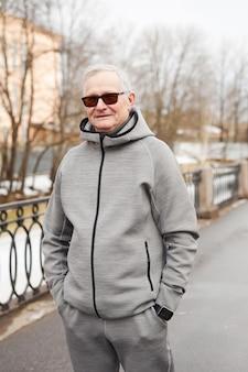 Taille verticale portrait d'un homme âgé de modem regardant la caméra en se tenant debout à l'extérieur en hiver