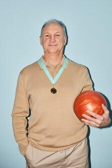 Taille verticale portrait of smiling senior man holding bowling ball en se tenant debout sur fond bleu, tourné avec flash
