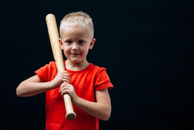 Taille vue portrait du joueur de baseball mignon petit garçon tenant une batte et regardant la caméra. isolé sur fond noir. concept d'enfance et de sport