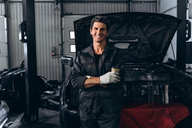 Taille vue portrait du mécanicien automobile debout près d'une voiture ouverte à l'extérieur et tenant une clé. concept de réparation de voiture