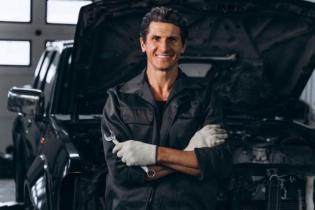 Taille vue portrait de l'homme mécanicien automobile senior posant avec une clé à l'atelier avec une voiture ouverte à l'arrière-plan. concept de service, de réparation, d'entretien et de personnes de voiture