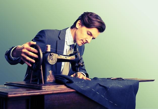 Tailleur au travail. jeune tailleur confiant cousant des vêtements à la boutique de tailleur