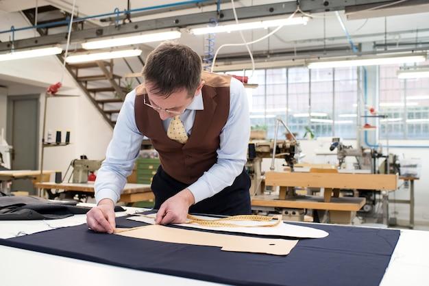 Tailleur établissant des patrons de papier sur un tissu bleu