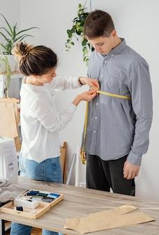 Tailleur féminin mesurant la chemise des clients masculins