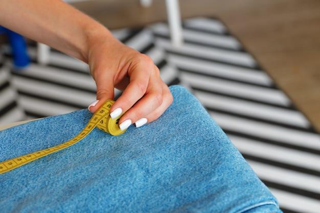Tailleur femme faisant des mesures avec du ruban à mesurer dans son bureau