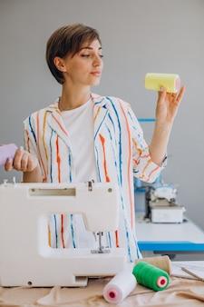 Tailleur femme tenant la machine à coudre