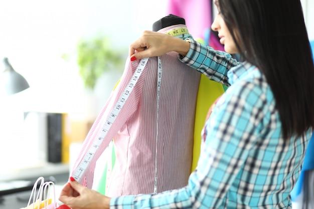 Tailleur femme tient un ruban à mesurer