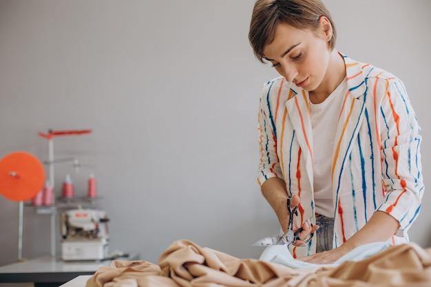 Tailleur de femme travaillant avec du tissu et des ciseaux