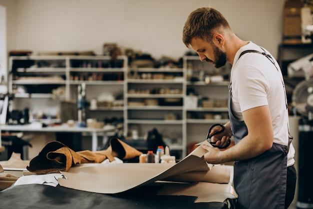 Tailleur homme travaillant avec du tissu en cuir