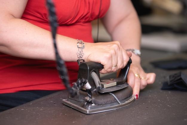Tailleur méconnaissable en train de repasser des vêtements avec du fer forgé à l'ancienne dans un atelier traditionnel.