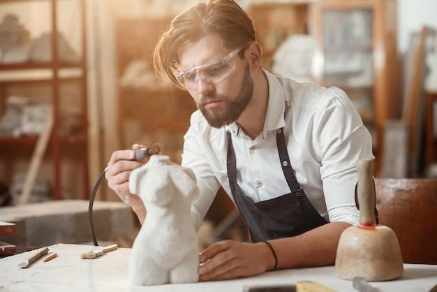 Tailleur de pierre attentif avec une barbe élégante dans des lunettes de protection détaillant la sculpture créative du torse de la femme sur son lieu de travail.