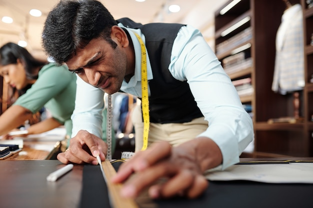 Tailleur précis dessinant une ligne lisse le long de la règle sur un tissu noir avec de la craie blanche