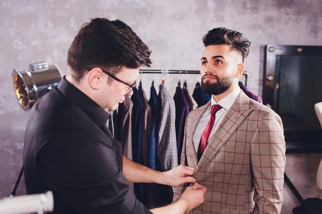Tailleur professionnel prenant des mesures pour le costume de couture dans un magasin de tailleurs