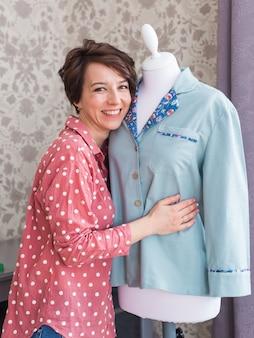 Tailleur tenant une chemise sur mannequin dans un studio de design créatif à domicile