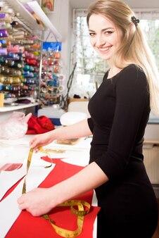 Tailleur travaillant avec du tissu à table dans l'atelier.