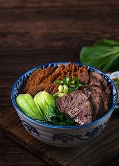 Taïwanais célèbre nouilles de boeuf alimentaire avec des tranches de jarret de boeuf braisé, tripes et légumes sur fond de table en bois