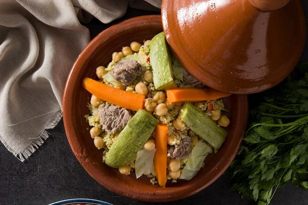 Tajine traditionnelle aux légumes, pois chiches, viande et couscous sur ardoise noire. vue de dessus