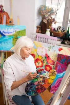Talentueux et célèbre. artiste aux cheveux blonds talentueux et célèbre âgé assis près de la toile et travaillant