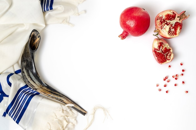 Talit, shofar, grenade et graines de grenade, sur fond blanc, vue du dessus