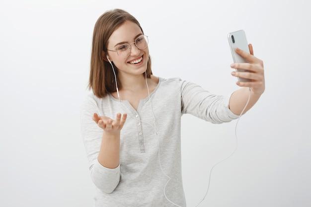 Talkign fille avec un ami via un message vidéo faisant des gestes avec la main pendant une conversation amusante pointant la caméra du smartphone au visage portant des écouteurs et souriant à l'écran de l'appareil sur un mur gris