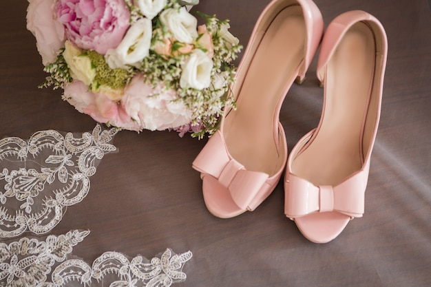 Talons hauts roses à la mode élégante avec un arc sur la salle de fond, glamour, mariée, mariage