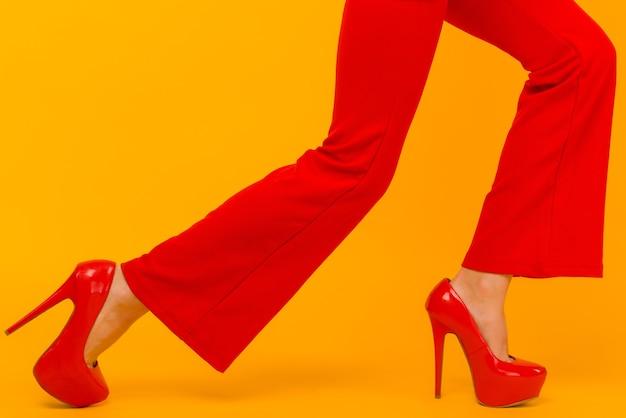 Talons et pantalons rouges élégants sur de fines jambes féminines