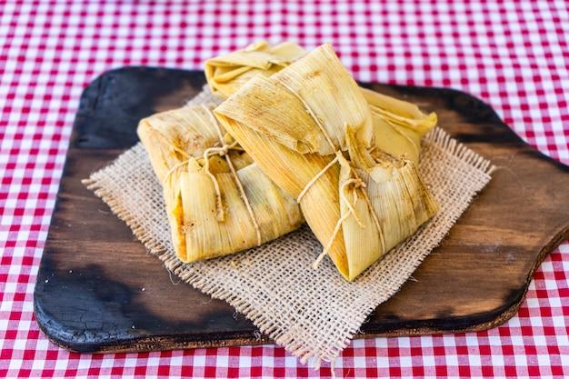 Tamales traditionnels andins de maïs et de viande servis sur une planche en bois. cuisine régionale.