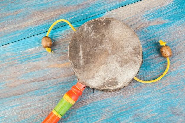 Tambour à main marocain vintage pour enfants sur fond de bois bleu.