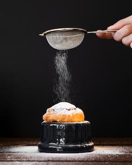 Tamis laissant tomber le sucre sur pain aux raisins