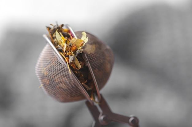 Tamis métallique avec tisane séchée dans une tasse en verre
