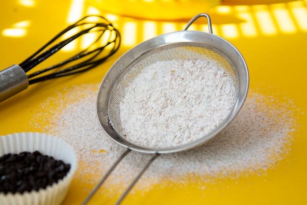 Tamiser avec de la farine entassée sur fond jaune.