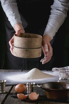 Tamiser la farine par des mains féminines