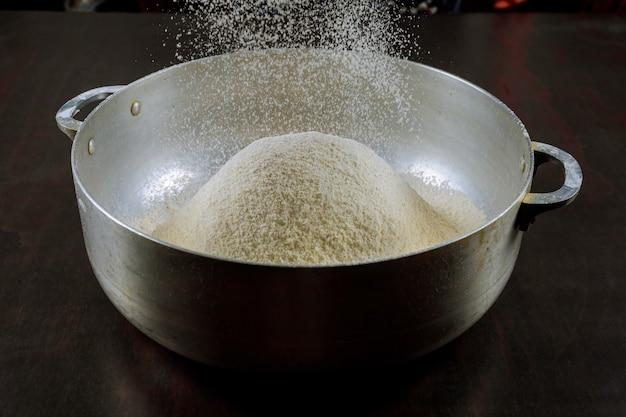Tamiser la farine avec un tamis pour faire de la pâte