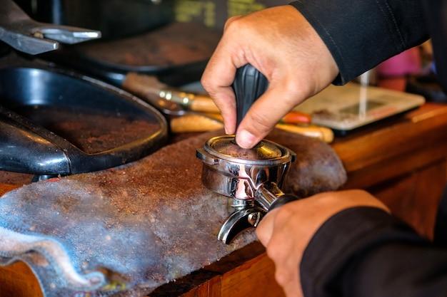 Tamper barista à main en appuyant sur le café en poudre dans un moulin à café