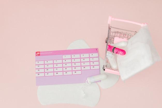 Tampon, féminin, serviettes hygiéniques pour les jours critiques, calendrier féminin, analgésiques pendant les menstruations sur un mur rose. suivi du cycle menstruel et de l'ovulation
