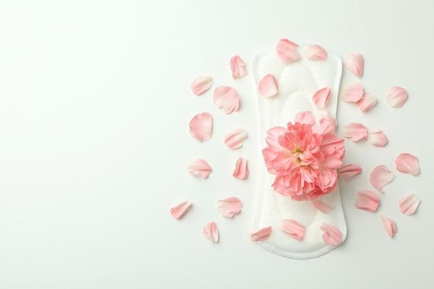 Tampon hygiénique avec fleur et pétales sur blanc