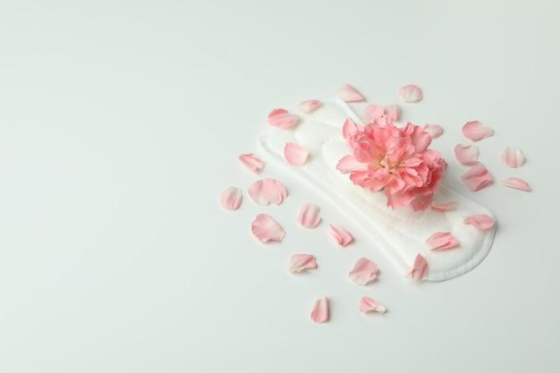 Tampon hygiénique avec fleur et pétales sur fond blanc