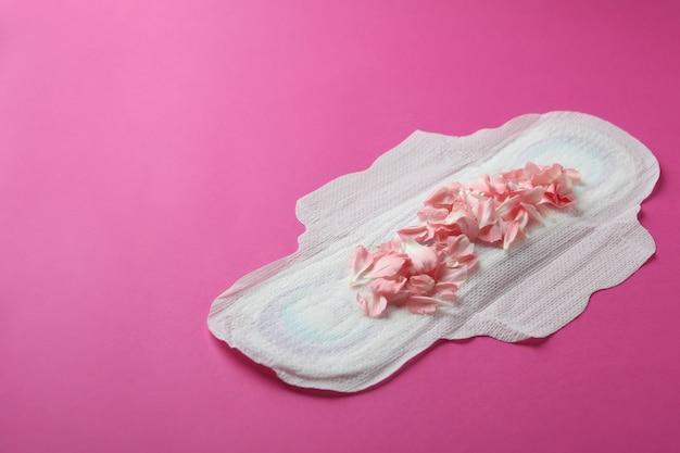 Tampon hygiénique avec pétales sur fond rose