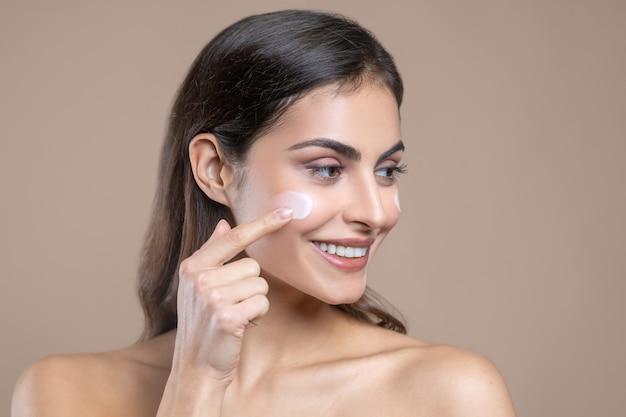 Tamponnez la crème. photo en gros plan d'une jolie femme aux cheveux longs appliquant de la crème sur sa joue avec son doigt de bonne humeur