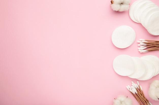 Tampons cosmétiques jetables hygiéniques et fleur de coton sur rose. vue de dessus