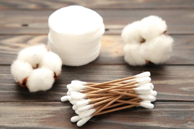 Tampons cosmétiques jetables hygiéniques et fleur de coton sur une surface brune