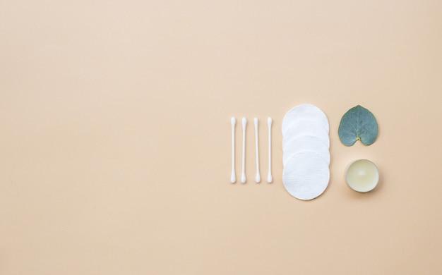 Tampons de coton et feuilles d'eucalyptus fraîches sur fond beige. mise à plat, vue de dessus, espace de copie. soins de santé des femmes