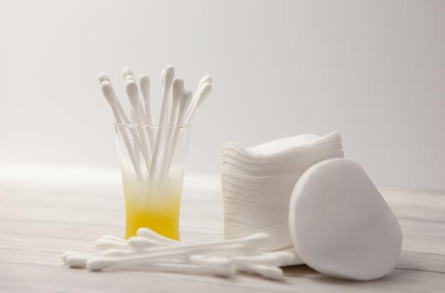 Des tampons de coton propres et des bâtons dans un verre pour le corps sur fond clair