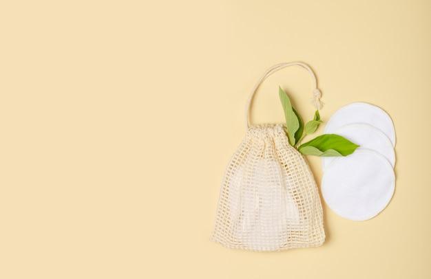 Tampons démaquillants réutilisables en coton dans un sac en tissu sur fond beige. le concept d'écologie et de consommation consciente. tampons en coton réutilisables
